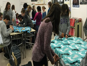 Shaker Junior High students from all four halls work to make blankets for rescued dogs.