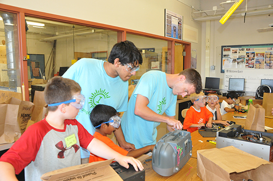 Shaker HS technology teacher and Camp Invention Director Brian Ashline works with students as a high school leadership intern looks on.