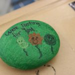 "A rock painted green with flowers on it that says ""we're rooting for you"""