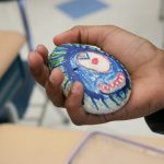 A students hand holding a rock that's painted like a one eyed monster