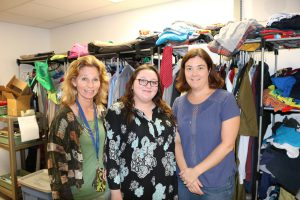 Three women stand in front of a closet organizer with clothes on it.