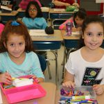Two girls sit at desks with boxes of crayons