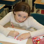 A girl colors on a sheet of paper
