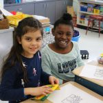 Two girls smile while one holds a box of crayons