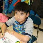 A boy colors holds a green pencil and draws on a sheet of paper