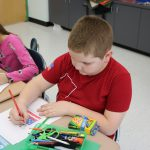 A boy holds a red pencil and colors a piece of paper
