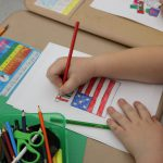 an arm with a red pencil colors in an American flag