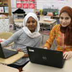 Two girls sit at desks with Chromebooks in front of them