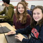 Two girls sit at desks with chromebooks and look sideways