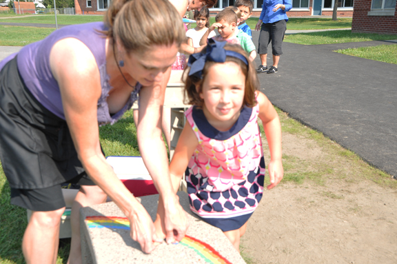 A Blue Creek Elementary students places her thumprint on the school's new Buddy Bench.