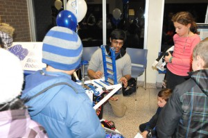 A member of the Shaker High School Robotics Team shows students the team's robot.