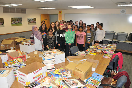 Student volunteers help sort 5,000 donated books.