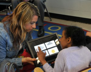 A student predicts the weather using an iPad with support from an educator.