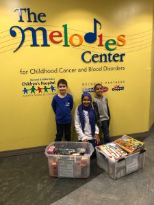 three students stand in front of the melodies center sign with boxes of toys and gifts in front of them