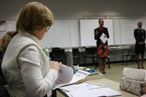 A woman sits sideways at a desk and a woman stands in the front of a room holding a piece of paper.