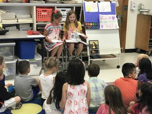 Two third grade students teach an art lesson to kindergarten students