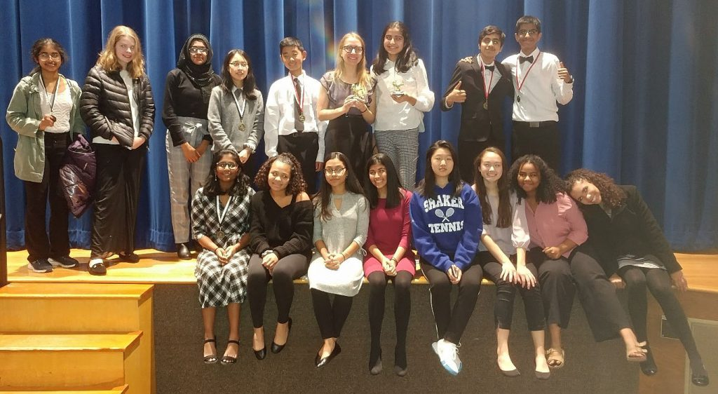 Speech and Debate students standing and sitting on a stage gathered together.