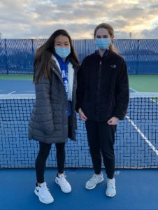 Two students standing on tennis court with masks on