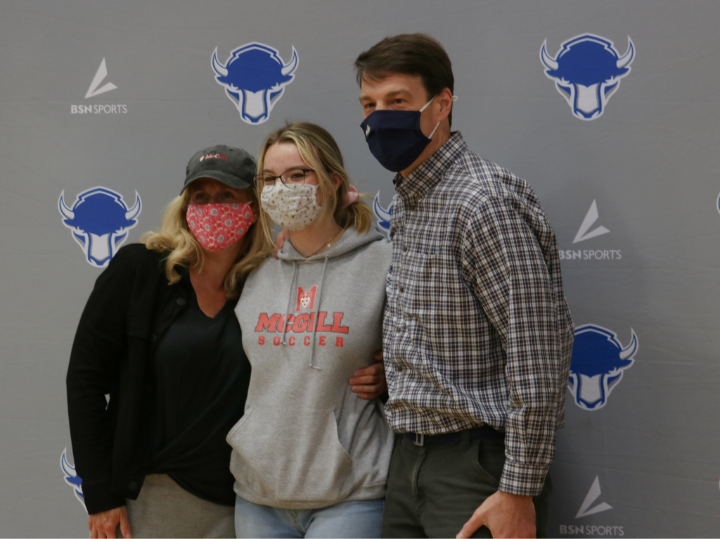parents hugging their child who just signed to play soccer in college