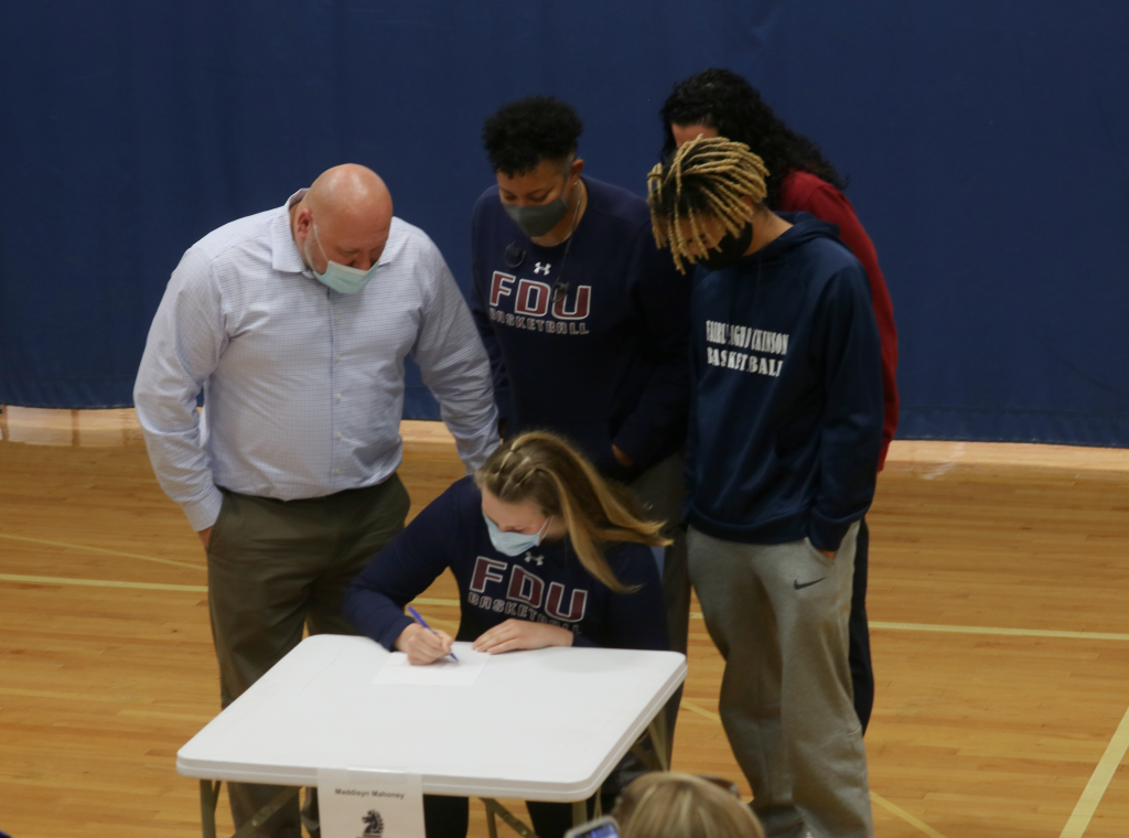 student signs commitment letter to play basketball with her family looking down at her signature