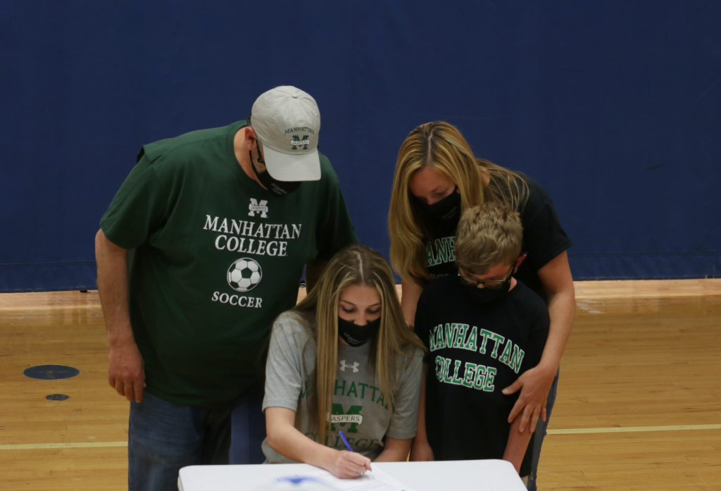 student signs with dad, mom, brother looking over her shoulder